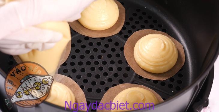 Giữ 'phễu' nặn bánh ở một vị trí cố định để nặn bánh theo hình 'ụ'